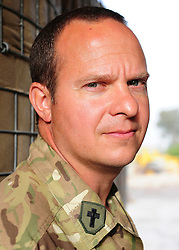 "© licensed to London News Pictures. HELMAND, AFG  21/04/11. Padre Robin Richardson. A British Army chaplain from Sidmouth who is due to finish his tour this Easter Sunday has proved a hit with paratroopers in Helmand Province, handing out crosses made from the wire-mesh that surrounds their base. Padre Robin Richardson (40) a member of 3rd Battalion The Parachute Regiment, has been serving in Afghanistan for the last six months. ""Towards the beginning of the tour, some of the lads asked me if I had some crosses I could give them,"" he said. ""I found a few at Camp Bastion, and I gave them out. I ran out very quickly.""..""So I wandered around our camp at Shahzad, trying to find something I could fashion into a cross. I noticed some discarded Hesco wire, and I saw lots and lots of crosses"". The wire normally makes up part of the Hesco Bastion fortified walls,  mesh containers with thick liners filled with gravel - that surround military bases across Afghanistan. ""I got busy with some bolt-cutters and a hammer and a drill,"" said Robin. ""And I started making small crosses out of the discarded wire.""..""A lot of the lads have asked if they can have one,"" he said. ""And they've been wearing them, and understanding a bit about what lies behind it"". Robin will be returning home to be reunited with his family after six months. ""I've got three sons, aged 13, 11 and 7, and they're fab,"" he said. ""They give my heart a reason for beating every morning"". ""The thing I've missed the most has been their smiles"" he added. ""The first thing I'll do when I get home is give them a hug"".. Please see special instructions for usage rates. Photo credit should read SGT Alison Baskerville/LNP"