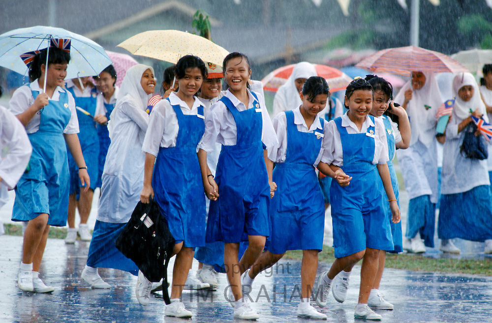 Schoolgirls caught in a downpour of rain in Singapore