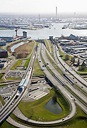 Nederland, Zuid-Holland, Schiedam, 04-03-2008; autosnelweg A4 met op- en afritten, toerit naar de Beneluxtunnel; rivier de Nieuwe Maas aan de horizon, methet hoofdkantoor van de Mammoet-van Seumeren Group (Groep) -  naast de rode kraan; links in beeld de metrolijn naar Hoogvliet (Calandlijn) met station Vijfhuizen en het het bedrijventerrein Vijhuizen (op  het terrein van de voormalige werf Wilton-Fijenoord); aan de horizon - met schoorstenen de Shell olieraffinaderij in Pernis;  A4 motorway with exit and entry, ramps to the Benelux Tunnel entrance, River Maas on the horizon, with the headquarters of the Mammoet- or Seumeren Group (Group)on the horizon - chimneys with the Shell oil refinery in Pernis.    .luchtfoto (toeslag); aerial photo (additional fee required); .foto Siebe Swart / photo Siebe Swart