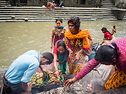 03 AUGUST 2015 - KATHMANDU, NEPAL:      People pray on the banks of the Bagmati River at Pashupatinath, a complex of important Hindu temples in Kathmandu. The Bagmati River runs through the complex. It is Nepal's most holy river, and this stretch of the river is like Varanasi in India. The river bank is lined with cremation ghats. Many Hindus, from both Nepal and India, make pilgrimages to Pashupatinath.   PHOTO BY JACK KURTZ