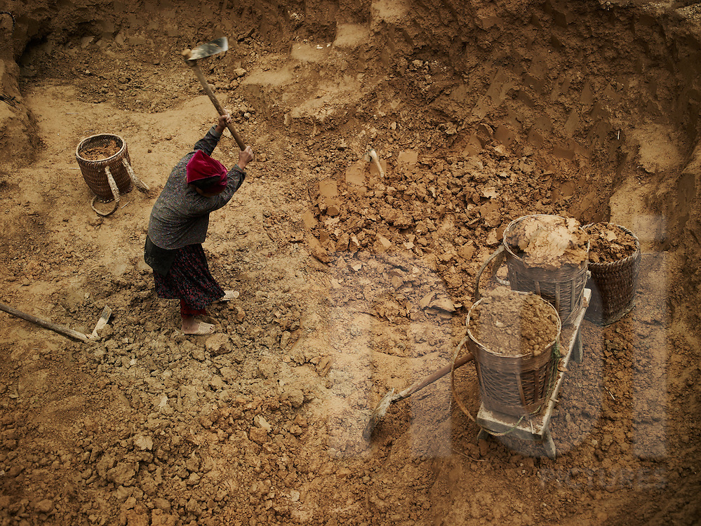 An ethnic woman  extract mud with a spade. She stands in a big hole close to wicker baskets loaded with soil. Ha Giang province, Vietnam, Asia