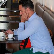 NLD/Amsterdam/20130701 - Keti Koti Ontbijt 2013 op het Leidse Plein, Freek Bartels geniet van kopje koffie en bekijkt zijn telefoon