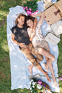 Young couple lying down on picnic rug in eachothers arms. Viewed from overhead.