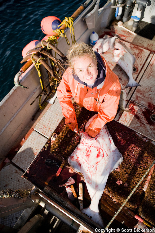 Emma Teal Laukitis gutting halibut while commercial longline fishing for pacific halibut in the Aleutian Islands, Alaska.