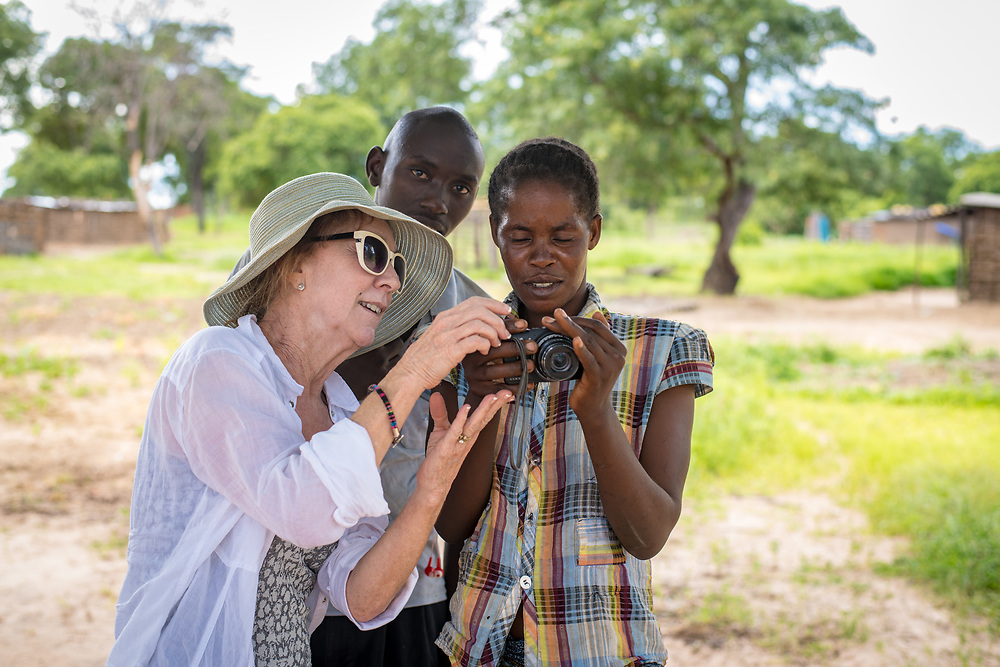 A people gather together to view something on a camera in Livingstone, Zambia