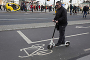 A man on a scooter passes over a bike stencil in a dedicated cycling lane at the northern end of Westminster Bridge, on 7th February 2019, in Westminster, London England.