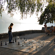Two young women playing chess on the Brienersee lake shore, Brienz, Switzerland