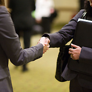 """Handshakes"" - Angela Waksmunski, a staffing manager with Ajilon, a ""specialized"" finance staffing and recruitment agency, greets unidentified job seekers at a job fair in Arlington, VA on Friday, Jan. 15, 2010."