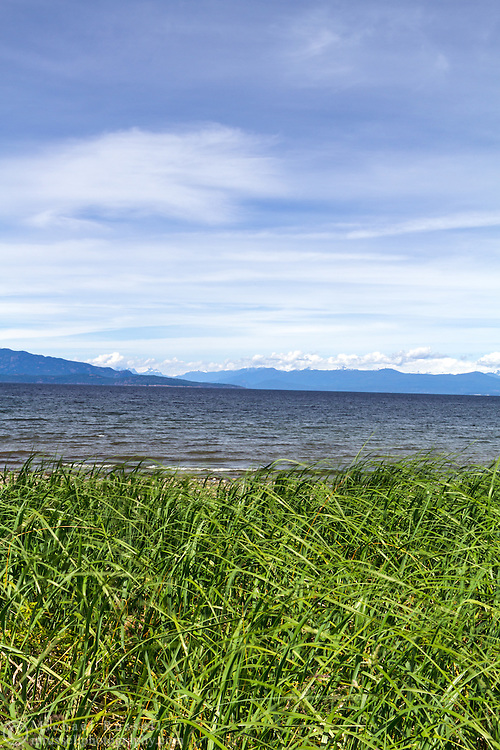 The Coast Mountains, Straight of Georgia and the shoreline grasses at Rathtrevor Beach Provincial Park in Parksville, British Columbia, Canada