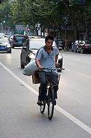 chinese man cycling with load in Shanghai China