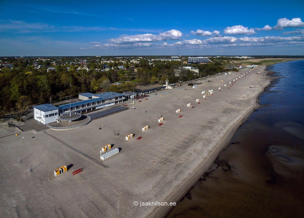 Row of dressing cabins on empty sandy Pärnu beach in Estonia. Waterfront, aerial. Sunset club.