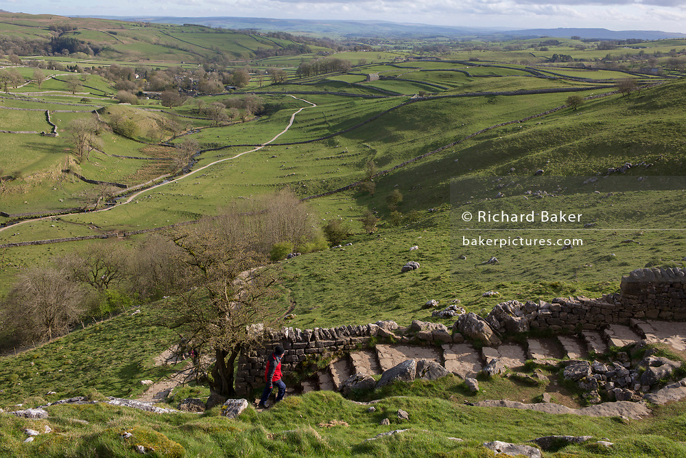 A walker near Malham Cove in the Yorkshire Dales National Park, on 12th April 2017, in Malham, Yorkshire, England.