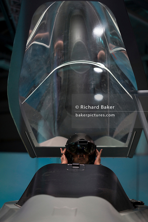 A visitor to the BAE Systems exhibition hall sits in a mock-up of the Tempest fighter, a replacement for the Typhoon, in the company's exhibition hall at the Farnborough Airshow, on 18th July 2018, in Farnborough, England.