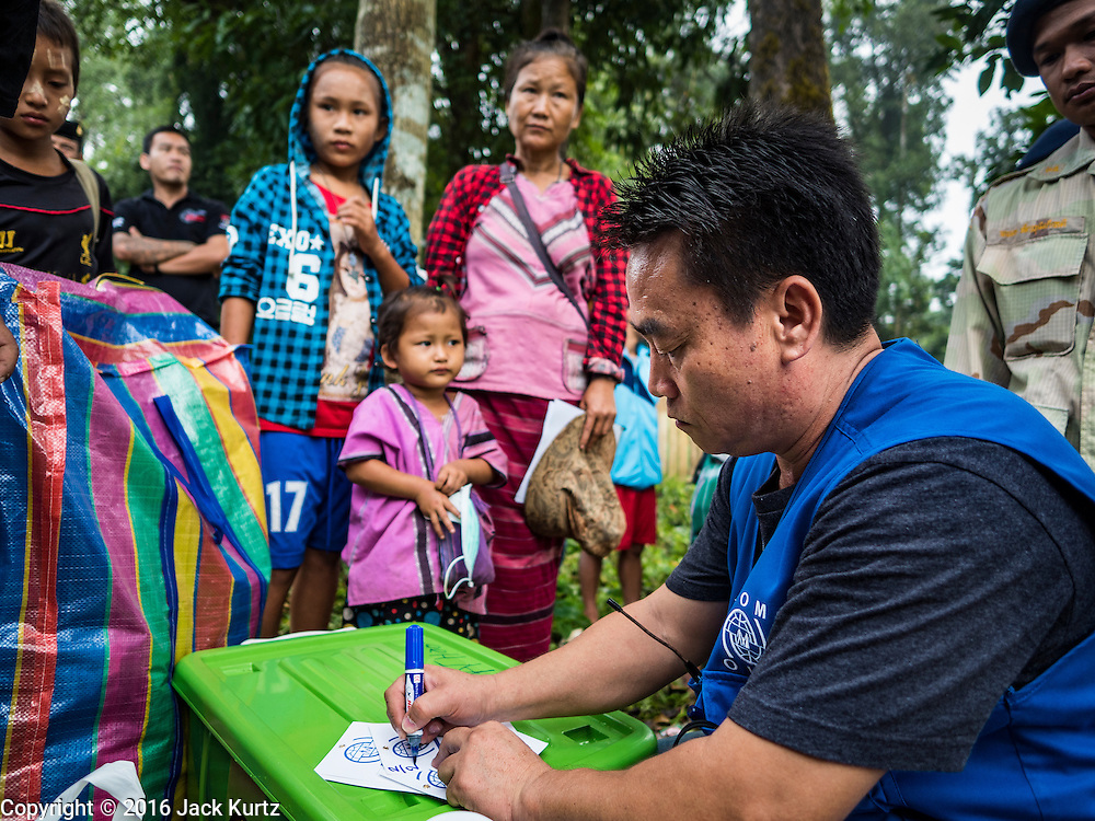 26 OCTOBER 2016 - NUPO TEMPORARY SHELTER, MAE CHAN, TAK, THAILAND: An IOM (International Organization for Migration) official helps Burmese refugees with last minute paperwork before they leave the Nupo Temporary Shelter refugee camp. Sixtyfive Burmese refugees living in the Nupo Temporary Shelter refugee camp in Tak Province of Thailand were voluntarily repatriated to Myanmar. About 11,000 people live in the camp. The repatriation was the first large scale repatriation of Myanmar refugees living in Thailand. Government officials on both sides of the Thai / Myanmar border said the repatriation was made possible by recent democratic reforms in Myanmar. There are approximately 150,000 Burmese refugees living in camps along the Thai / Myanmar border. The Thai government has expressed interest several times in the last two years in starting the process of repatriating the refugees.     PHOTO BY JACK KURTZ
