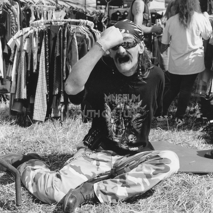 Toothless man wearing camouflage trousers at a Rock and Blues festival