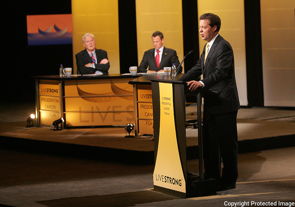 28 August 2007: MSNBC Hardball host Chris Matthews (left) and seven-time Tour de France winner Lance Armstrong (center) listen to Republican presidential hopeful and Senator Sam Brownback (R-KS) (right) delivers his opening statements at the LIVESTRONG Presidential Cancer Forum in Cedar Rapids, Iowa on August 28, 2007.