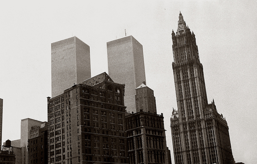 To the right is the old Woolworth Building. Built in 1913, it was formerly the tallest building in the world. To the left is the World Trade Center, as they both looked in 1978.