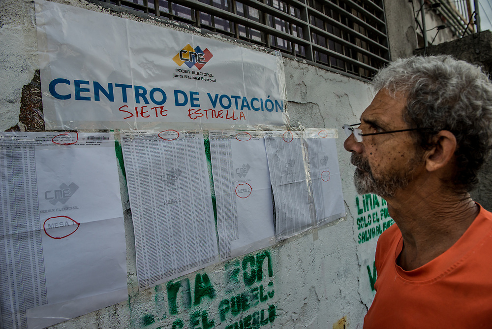 CARACAS, VENEZUELA - JULY 30, 2017:  Government supporters check an election registry to see which polling table to cast their vote at for the new National Constituent Assembly. Many fear this election will turn Venezuela similar to Cuba. Opponents of the government criticize President Maduro for calling for this election - saying the new assembly is a power grab, and will be a puppet of the President - the only candidates on the ballot are government loyalists. Critics also fear the new assembly will turn the country into a dictatorship, re-write the constitution and wipe out the democratically elected and opposition controlled congress. There have been widespread reports of voter intimidation, and of the government threatening state workers and citizens that receive government benefits like subsidized food - who report the government telling them they are obligated to vote, and if they don't, they will lose their jobs and benefits. Thousands have taken to the streets to protest the election in the days leading up to the July 30th vote.  PHOTO: Meridith Kohut for The New York Times