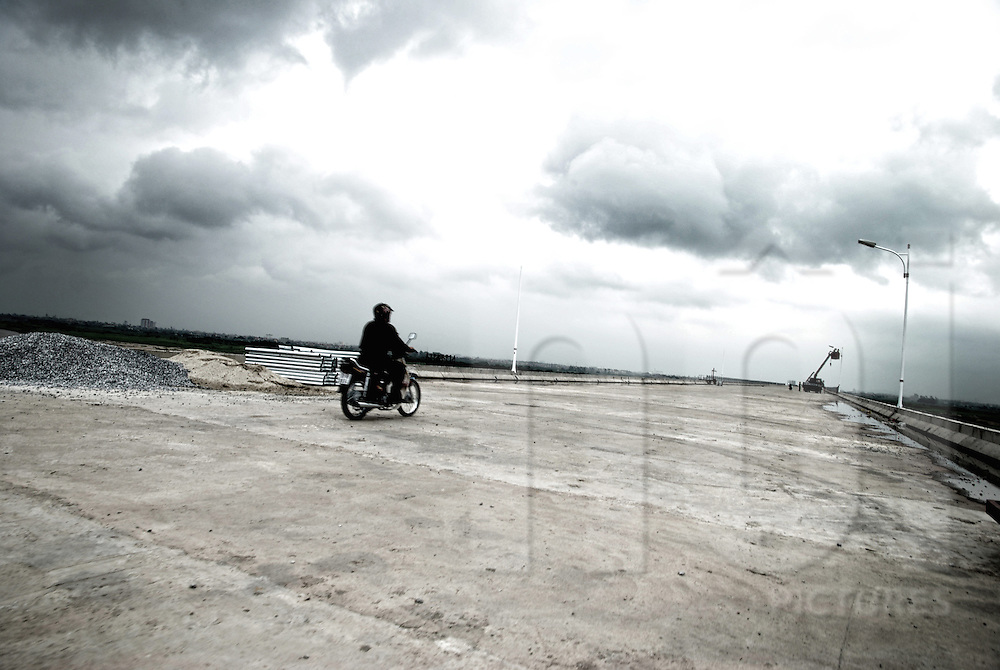 A vietnamese man rides a motorbike on a the unfinished bridge of Vinh Tuy by a stormy day. Hanoi, Vietnam, Asia