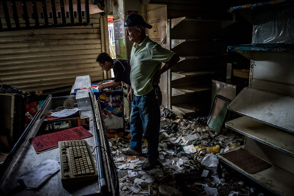 CARACAS, VENEZUELA - APRIL 21, 2017:  Workers inspect the damage to Vicruz supermarket, that was one of over a dozen stores looted late last night in El Valle, a working class neighborhood in Caracas. The streets of Caracas erupted into a night of riots, looting and clashes with National Guardsmen as anger from two days of pro-democracy protests spilled into unrest in working class neighborhoods and slums. Shots rang out throughout the night in El Valle, a neighborhood of mixed loyalties, as armored vehicles struggled to contain crowds of looters. At one point during the night, clashes became so heavy that a nearby children's hospital was evacuated after the ward filled with tear gas. The government said they were responding to an attack on the hospital by opposition protestors.  PHOTO: Meridith Kohut