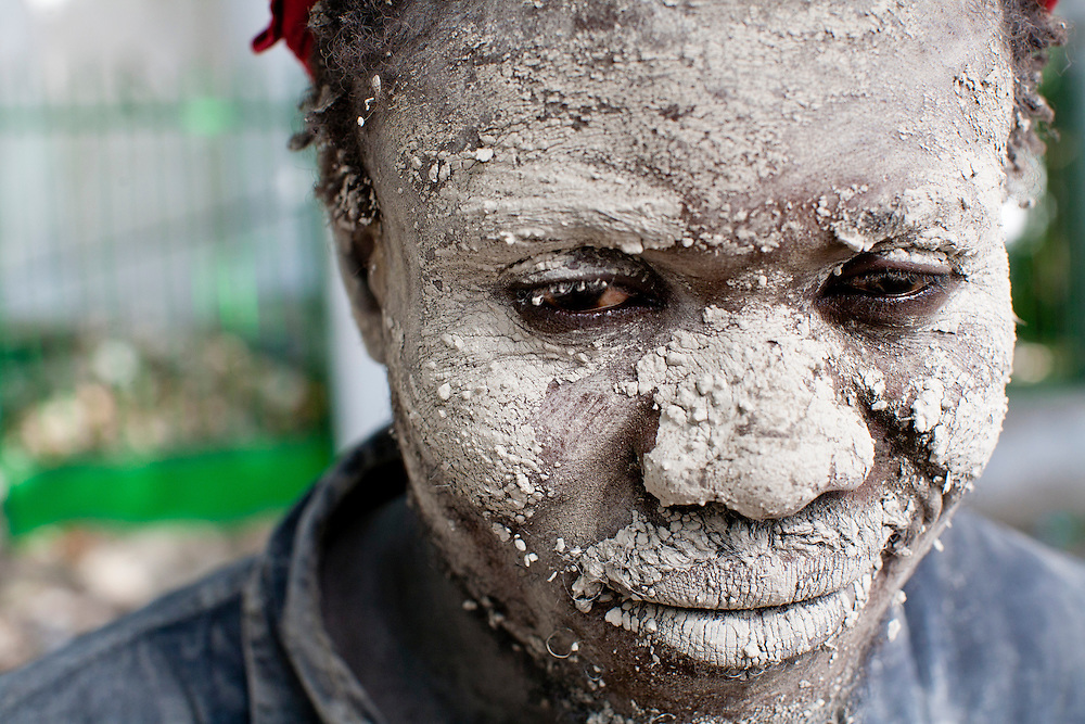 A man stands on the sidewalk with his face covered in mud on July 7, 2010 in Port-au-Prince, Haiti.