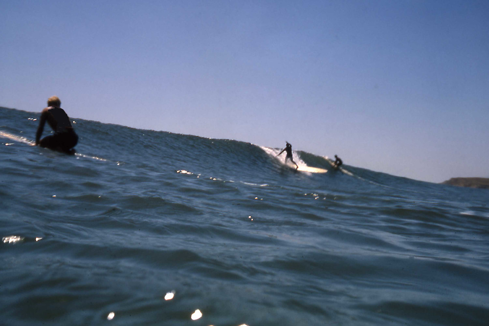 """Dewey Weber cranks off one his famous bottom turns at Rights and Lefts during one of our summer boat trips to the Racnh. In the foreground is my roommate Bob """"Porkchop"""" Barron. I had just gotten a Nikonos water camera and had started shooting from the water."""