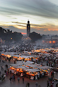 Evening view of stalls at Djemma el Fna square and marketplace, Medina, Marrakech, Morocco. The minaret of the Koutoubia mosque towers over the square. Picture by Manuel Cohen