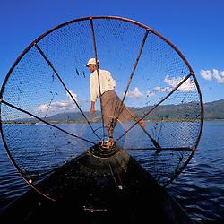 A leg rowing fisherman on the serene Inle Lake in Myanmar.