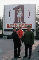 """1983, Beijing, China --- A Chinese couple with an infant daughter stand in front of a sign advocating family planning. The sign says """"Mama, Papa, and Me"""" and depicts a girl, conveying an unspoken message against the practice of female infanticide. --- Image by © Owen Franken"""