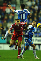 Photo: Paul Greenwood.<br />Wigan Athletic v Liverpool. The Barclays Premiership. 02/12/2006. Wigan's Paul Scharner, top, clatters into Liverpool's Steven Gerrard.