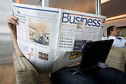 "In the British Airways Galleries First lounge at Heathrow Airport's Terminal 5, an unseen business passenger hides his face while reading the Business section of the Daily Telegraph. With his laptop perched across his knees the anonymous man sits by a window where natural light is a feature of this exclusive facility (only available to passengers travelling in First and Gold Executive Club members) designed by Artwise. The lounge's 15,000 sq ft complex was built at the cost of £60 million. From writer Alain de Botton's book project ""A Week at the Airport: A Heathrow Diary"" (2009). .."