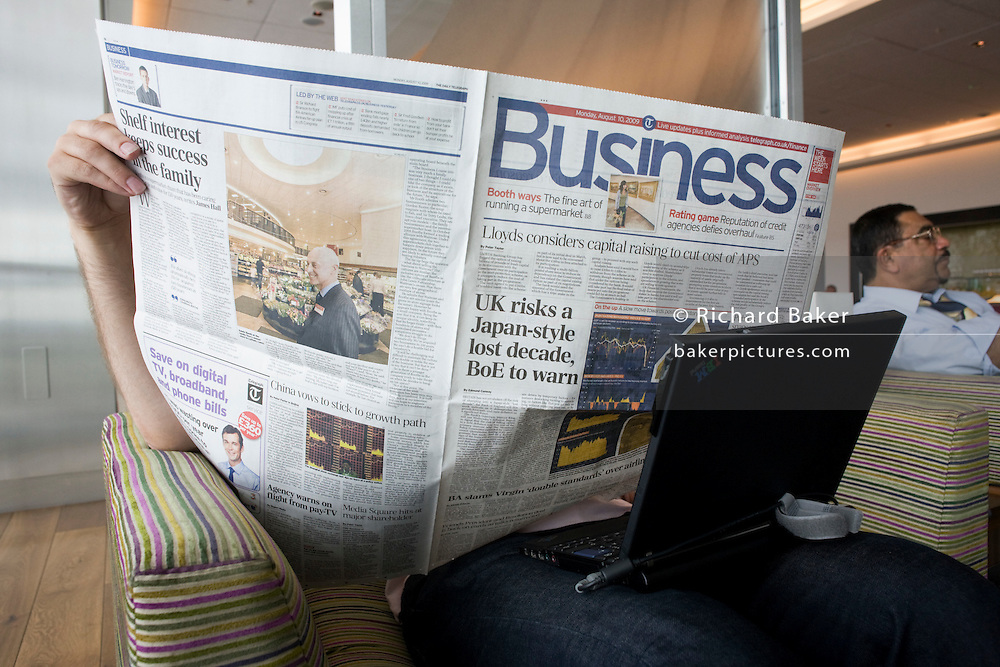 """In the British Airways Galleries First lounge at Heathrow Airport's Terminal 5, an unseen business passenger hides his face while reading the Business section of the Daily Telegraph. With his laptop perched across his knees the anonymous man sits by a window where natural light is a feature of this exclusive facility (only available to passengers travelling in First and Gold Executive Club members) designed by Artwise. The lounge's 15,000 sq ft complex was built at the cost of £60 million. From writer Alain de Botton's book project """"A Week at the Airport: A Heathrow Diary"""" (2009). .."""