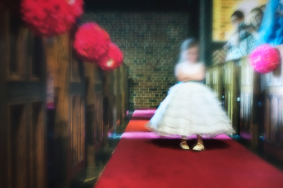 The young ring bearer slowly makes her way down the aisle in her Mary Janes. Delicately crossed arms and a methodical gait.