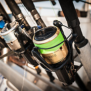 Close-up of fishing reels lined up with rods in their holsters on Australia's Great Barrier Reef.