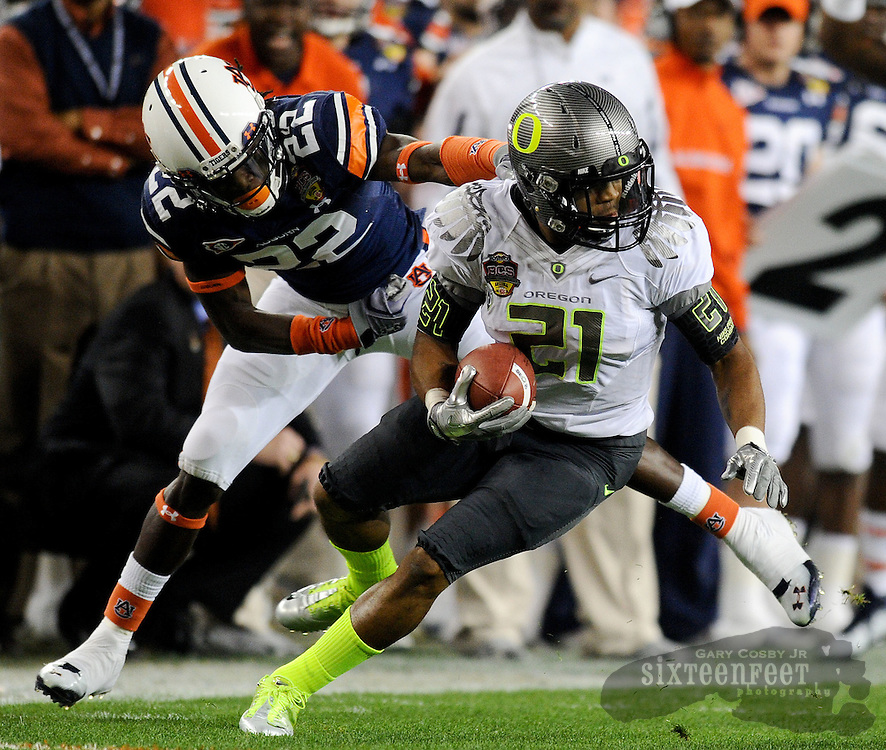 Daily Photo by Gary Cosby Jr.   ..Auburn defender T'Sharvan Bell slides off of Ducks running back LaMichael James during the first half of the BCS National Championship Game in Glendale, AZ.