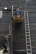 A workman kneels on a pallet, raised at its maximum height limit up on a forklift and at the top of a ladder while brushing down an old clapboard warehouse, on 29th May 2019, in Faversham, Kent, England.