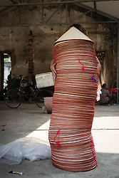 "Hands hold an unsteady stack of conical hats, Chuong Village, Ha Tay Province, Vietnam, Southeast Asia, 2013. This handicraft village specializes in the fabrication of the conical hat, known as ""non"" in Vietnamese."