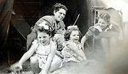mother toddler twins and young child playing in the sand 1950