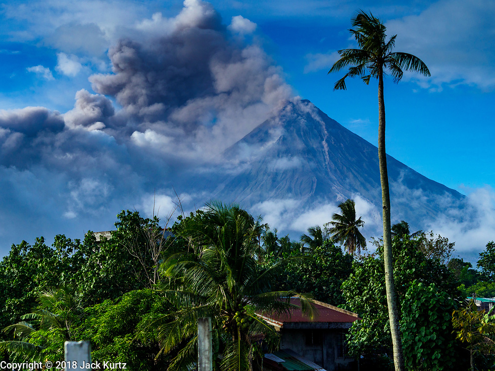 "22 JANUARY 2018 - LEGAZPI, ALBAY, PHILIPPINES: A late afternoon eruption of the Mayon volcano as seen from Legazpi, about 12 kilometers from the volcano. There were a series of eruptions on the Mayon volcano near Legazpi Monday. The eruptions started Sunday night and continued through the day. At about midday the volcano sent a plume of ash and smoke towering over Camalig, the largest municipality near the volcano. The Philippine Institute of Volcanology and Seismology (PHIVOLCS) extended the six kilometer danger zone to eight kilometers and raised the alert level from three to four. This is the first time the alert level has been at four since 2009. A level four alert means a ""Hazardous Eruption is Imminent"" and there is ""intense unrest"" in the volcano. The Mayon volcano is the most active volcano in the Philippines. Sunday and Monday's eruptions caused ash falls in several communities but there were no known injuries.   PHOTO BY JACK KURTZ"