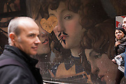 Tourists pass-by renaissance paintings on construction hoarding in Florence's Piazza degli Uffizi. .