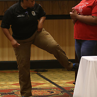 Lt. Katarsha White demonstrates a self defense move on attendee Uriah Coleman, 17 during the G.I.R.L. talk event