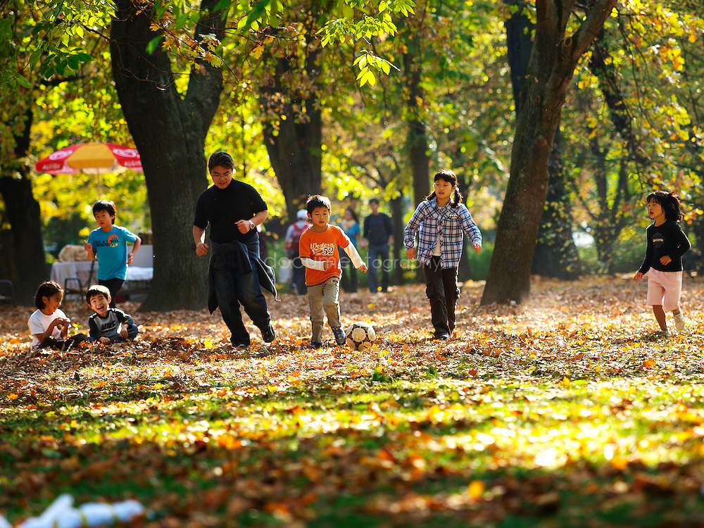 Asian children play football in Margaret Island park, Budapest, Hungary.