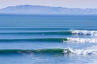 Three surfers riding waves during a big winter swell at Surfers Point in Ventura, California on January 20, 2013.