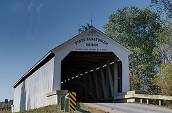 2015 Oct 19:   Parke County Indiana is the site of the Indiana Covered Bridge Festival every October.  This is the State Sanatorium Bridge.  It was Originally built on by J A Britton. It was relocated from private property and restored in 2009.  It now rests on County Road 100N over the Little Raccoon Creek.The bridge has a 154' span and is painted white.<br /> <br /> This image was produced in part utilizing High Dynamic Range (HDR) processes.  It should not be used editorially without being listed as an illustration or with a disclaimer.  It may or may not be an accurate representation of the scene as originally photographed and the finished image is the creation of the photographer.