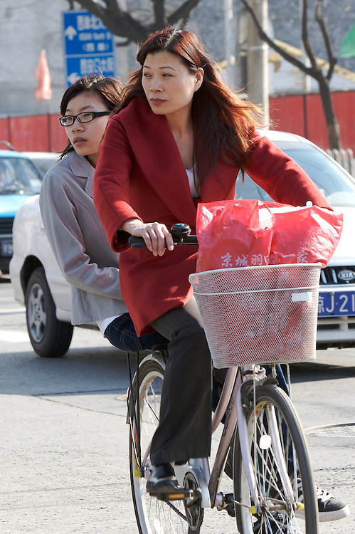 Two woman share a ride through the Xicheng District of Beijing, China.