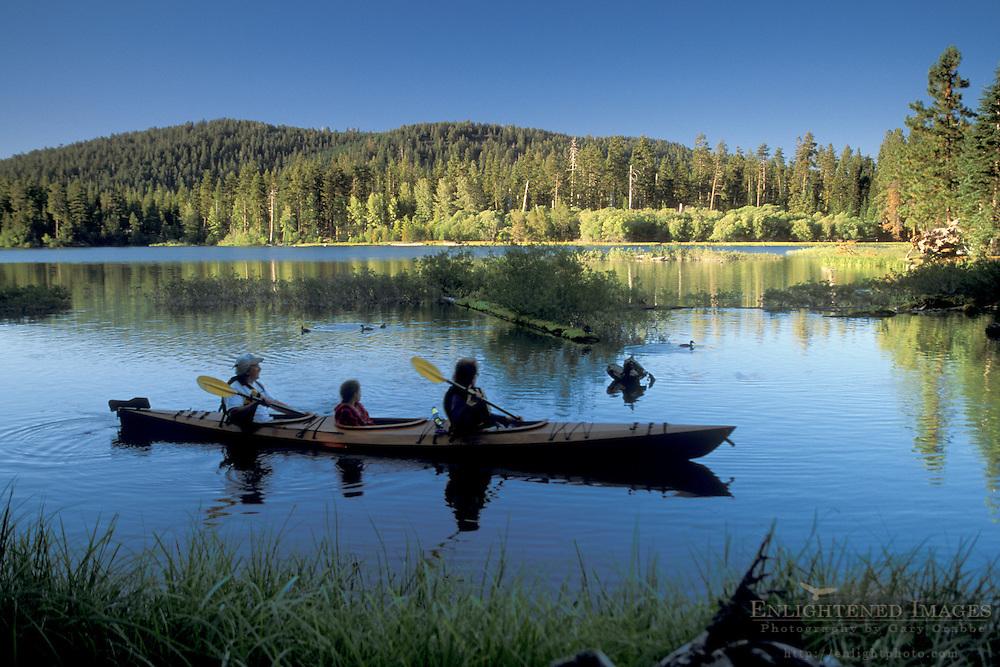 Family paddles homemade wooden kayak on blue water at Manzanita Lake, Lassen Volcanic National Park, California