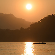 A lone small sampan crosses the river just before sunset on the Mekong River near Luang Prabang, Laos.