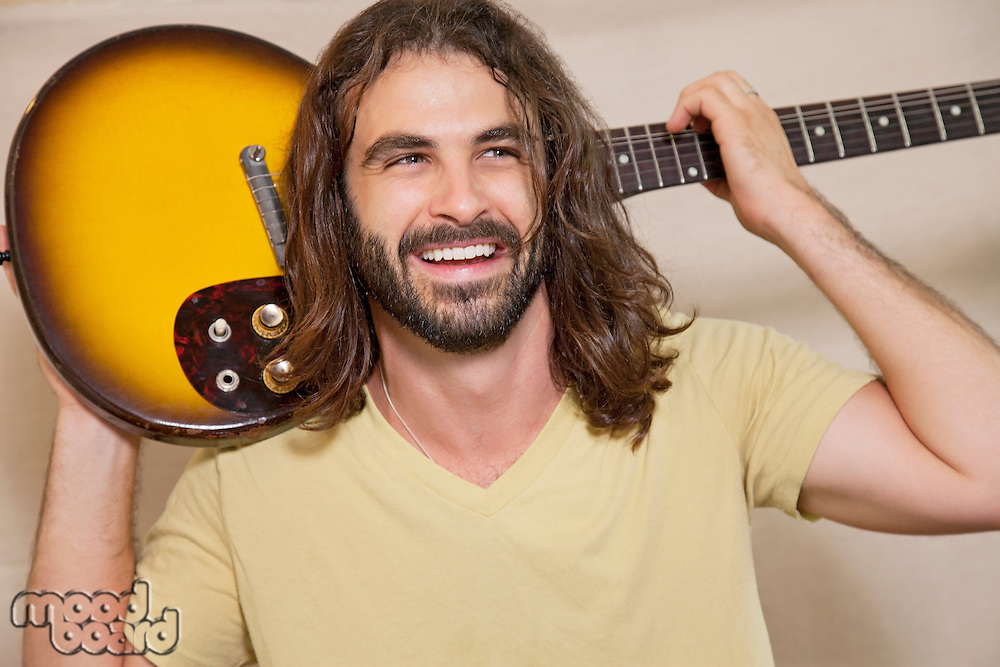 Happy man holding guitar on back of his shoulders