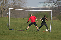 © Licensed to London News Pictures. 08/04/2020. London, UK. Two people set up temporary goal and play football on Hampstead Heath, North London, during a pandemic outbreak of the Coronavirus COVID-19 disease. The public have been told they can only leave their homes when absolutely essential, in an attempt to fight the spread of coronavirus COVID-19 disease. Photo credit: Ben Cawthra/LNP