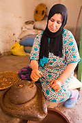 Mother and daughter Layla and Hanane grind the shelled and toasted argan nuts using a traditional grindstone to produce argan oil at their farm home in Agouni n Fad village near Aoulouz, Taliouine & Taroudant Province, Souss Massa Draa region of Southern Morocco, 2016-05-24. <br />